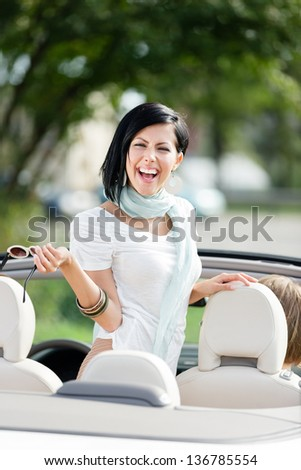 Lovely teenager stands in the car with the put off sunglasses