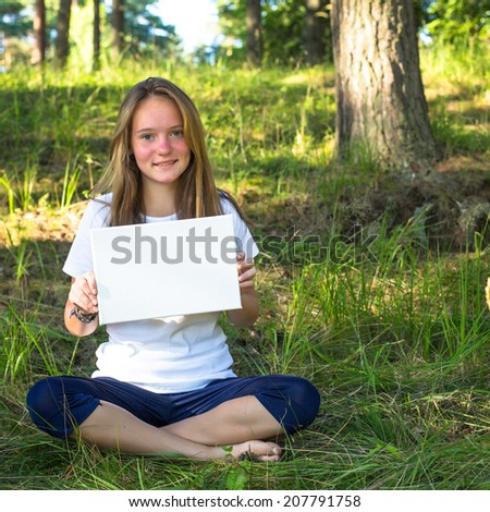 Lovely teengirl holding clean white sheet paper, in the park (banner for your message) - stock photo