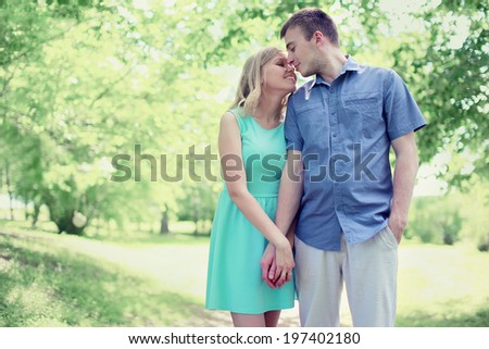 Lovely tender young couple in love walking in sunny spring park, soft colors - stock photo