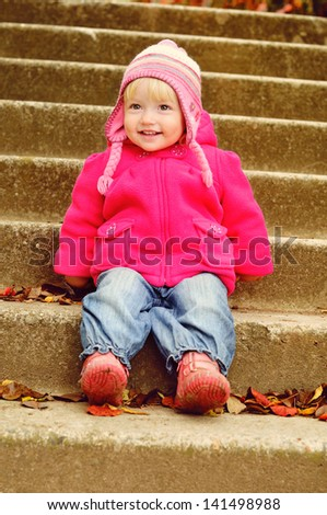 lovely toddler sitting on the stairs - stock photo