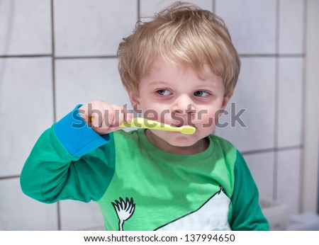 Lovely toddler with blue eyes and blond hair brushing his teeth