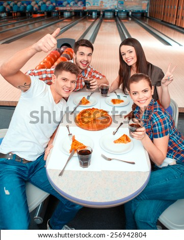 Lovely weekend. Top view image of young attractive woman and man-eating pizza and showing thumb up with bowling alley in the background  - stock photo