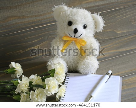 Lovely white bear, white carnation and white notebook on wooden table