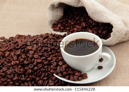 Lovely white cup of hot coffee and coffee beans - stock photo