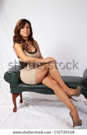 Lovely white woman with long brown hair, sitting on a bench seat with a friendly smile and eye contact with the camera and her legs crossed - stock photo