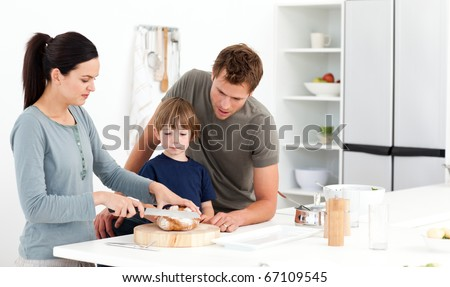 Lovely woman cutting bread for her son ad husband in the kitchen