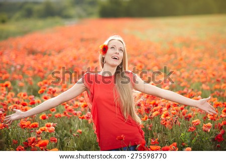 Lovely woman feeling happy on the poppy flower field. Beautiful woman in happiness and elated enjoyment with arms raised outstretched up enjoying nature, summertime leisure concept.  - stock photo