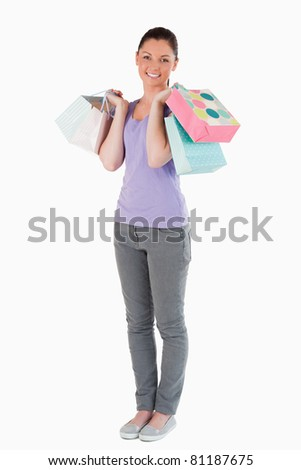 Lovely woman holding shopping bags while standing against a white background