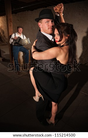 Lovely woman in black with male dancing partner performing tango - stock photo