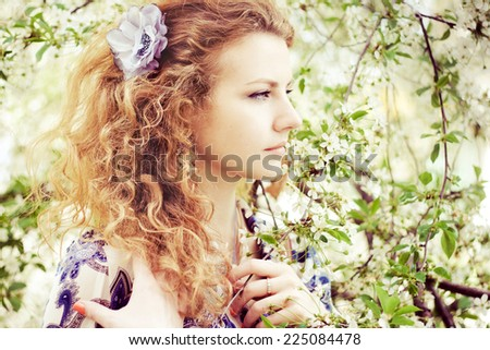 Lovely woman in spring bloom - stock photo