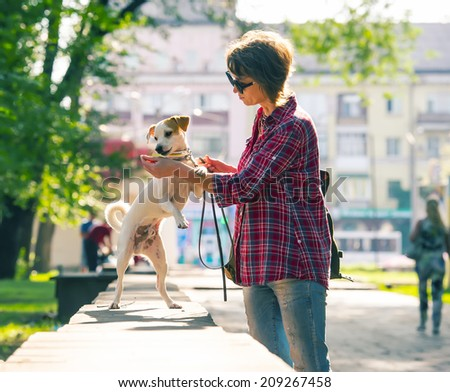Lovely woman in sunglasses walking in a city park with a dog - stock photo