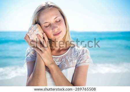 Lovely woman listening to a shell at the beach - stock photo
