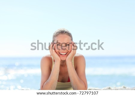 Lovely woman sunbathing at the beach - stock photo