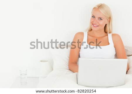 Lovely woman using a laptop in her bedroom - stock photo