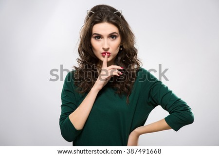 Lovely woman with big eyes and red lips wearing green sweater and metal ears on head, making a hush gesture, holding hand with red manicure near mouth and looking at camera, copy space. - stock photo