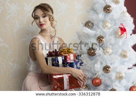 lovely woman with elegant style sitting indoor near decorated tree with some Christmas presents on her legs