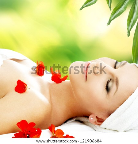 lovely woman with red flower petals in spa - stock photo