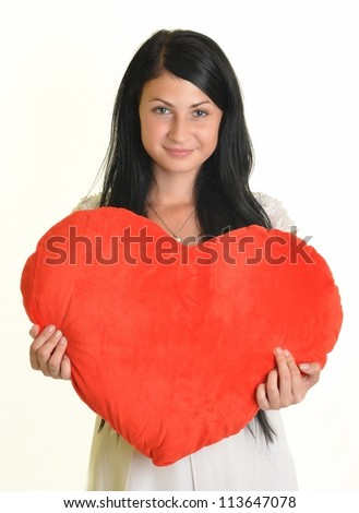 lovely woman with red heart-shaped pillow over white - stock photo