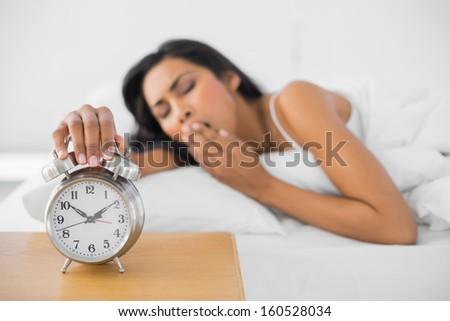 Lovely yawning woman turning off the retro alarm clock lying in her bed - stock photo