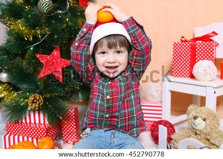 Lovely 2 years boy in Santa hat with tangerine - stock photo
