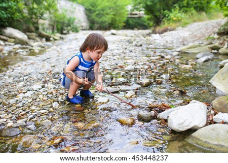 lovely 2 years toddler boy plays with stick in flashy river