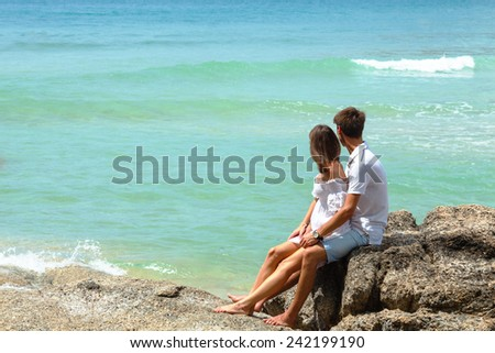lovely young adult couple on the rocks above tropical sea - stock photo