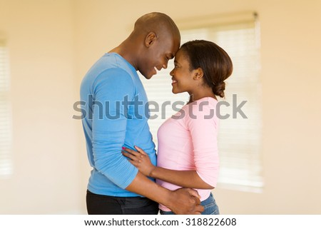 lovely young afro american couple embracing in their home - stock photo