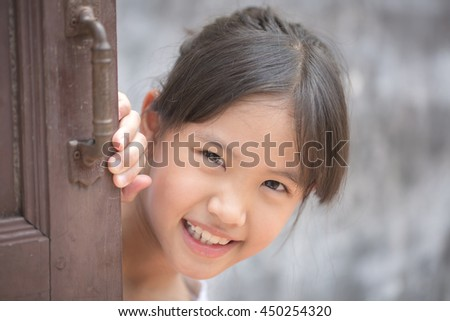 Lovely young Asian girl portrait playing hidden behind the wooden door - stock photo