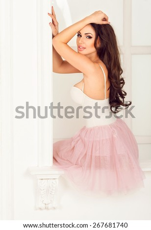 Lovely young beautiful sensual brunette woman in pink ballet skirt sitting on a white windowsill and looking at camera. Bright classical background - stock photo