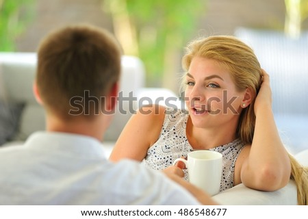Lovely young blonde woman straightens her blond hair sitting on a couch propped her head with one hand and holding a mug of delicious tea in another hand, in love looking at her husband