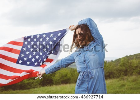 Lovely young brunette girl in denim dress and in sunglasses holding an american flag of independence.