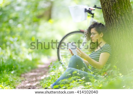 Lovely young brunette woman reading a book in a park, on a sunny day