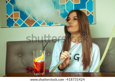 Lovely young brunette woman with green eyes smokes shisha and drinks cocktail