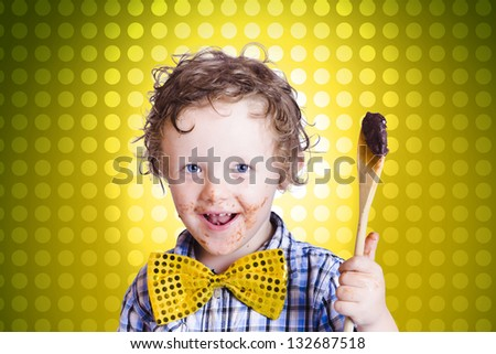 Lovely young child holding chocolate covered cooking spoon when mixing icing for an easter cake, on yellow polka-dot background - stock photo