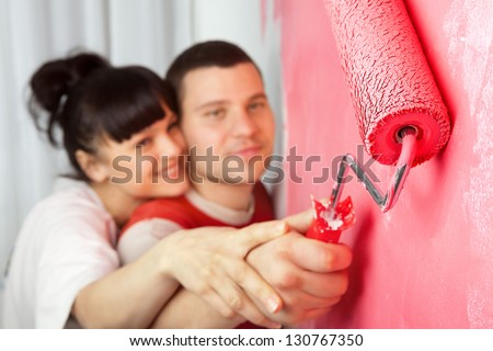 Lovely young couple of workers painting a wall with roller (focus on  roller) - stock photo