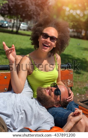 Lovely young couple resting together on a wooden bench in the park