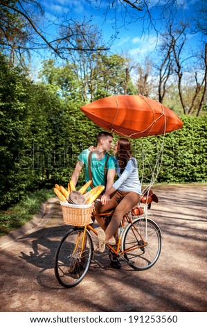 Lovely young couple riding and kissing on the bicycle with red dirigible and the basket full of baguettes in the park in the summer - stock photo