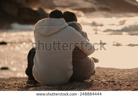 Lovely young couple sitting in front of the sea, selective focus - stock photo