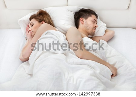Lovely young couple sleeping on the bed