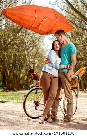 Lovely young couple standing and hugging near the bicycle with red dirigible in the park - stock photo
