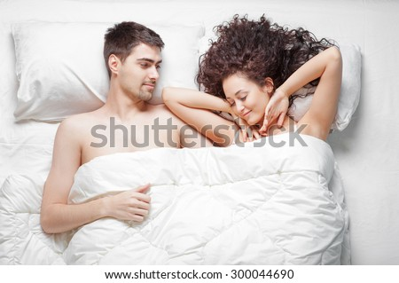 Lovely young couple waking up in bed at home. Young beautiful woman stretches her arms while man is smiling to her. - stock photo