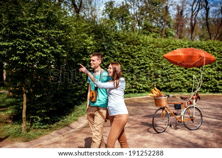 Lovely young couple walking in the park with the bicycle with red dirigible on the background  - stock photo
