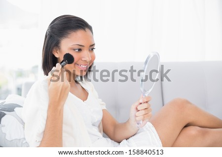 Lovely young dark haired woman in white clothes applying powder on her face in a living room