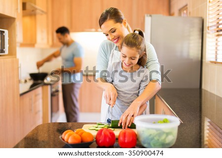 lovely young family preparing meal in kitchen - stock photo