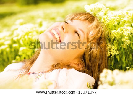 Lovely young girl relaxing on a meadow