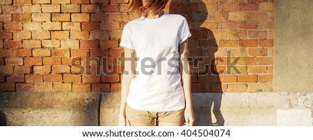 Lovely young girl wearing in a white blank t-shirt  posing against a background of a brick wall in the rays of the setting sun - stock photo