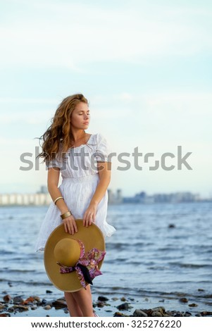 lovely young girl wearing white dress , holding wide-brimmed straw hat stay on the sea cost.