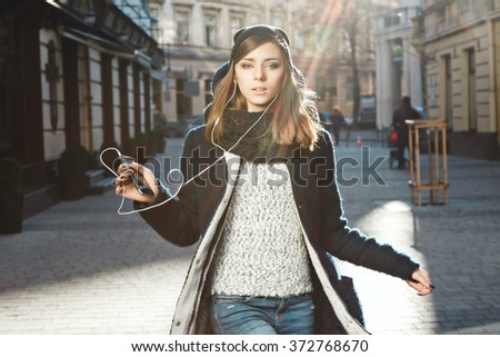 Lovely young girl with nude make up and brown hair wearing black coat and black scarf, wearing headphones and holding mobile phone, portrait.