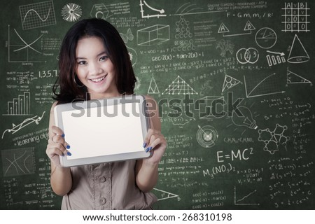 Lovely young high school student standing in the class and showing a blank tablet screen - stock photo