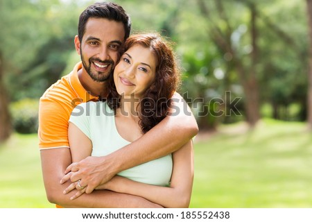 lovely young indian couple hugging outdoors - stock photo